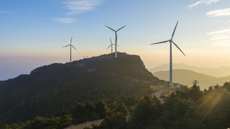 Windräder, die Strom erzeugen, im Sonnenaufgang.
